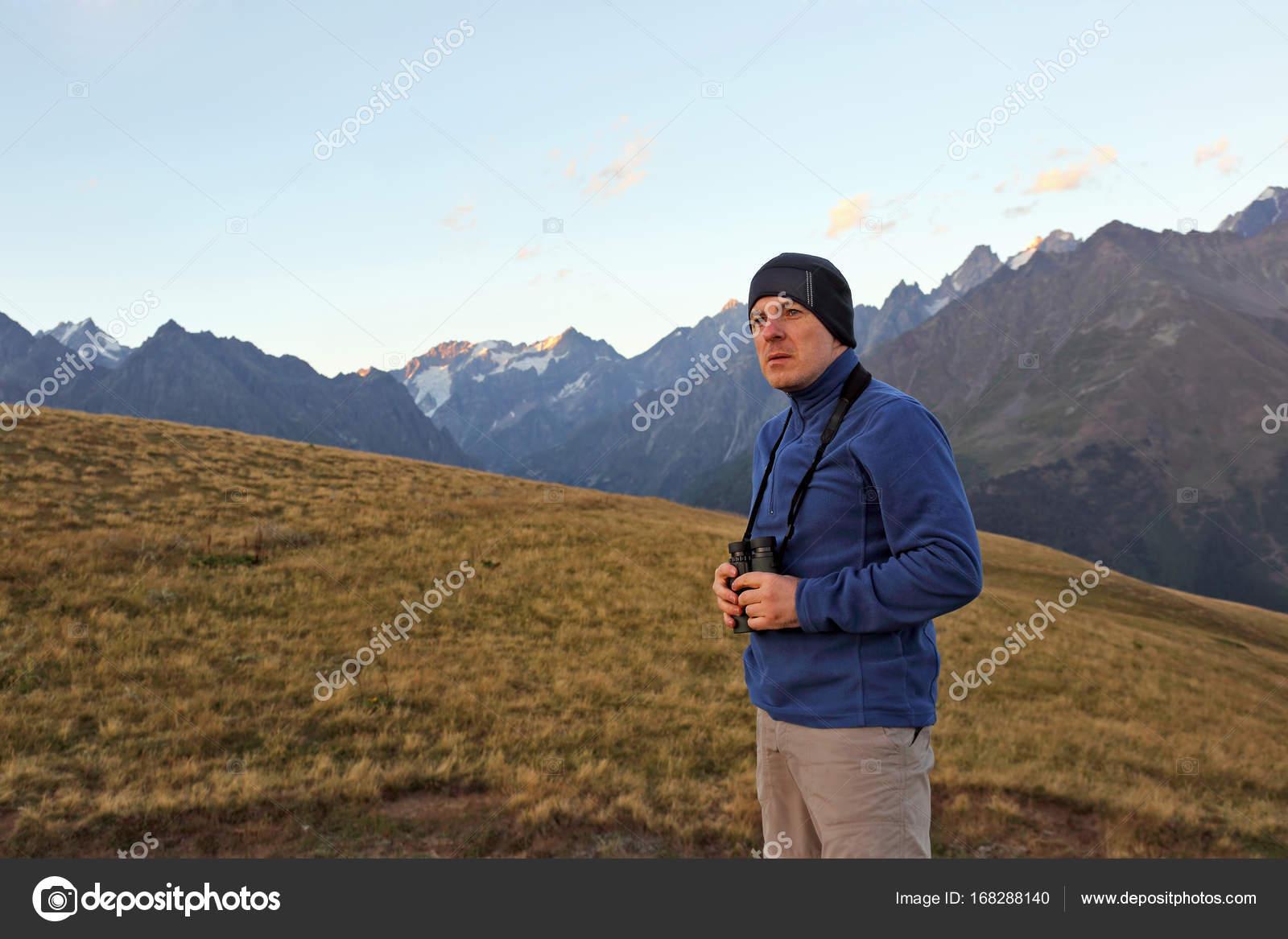 Wanderer mit dem fernglas steht vor dem hintergrund der berge