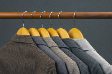 Different women's office classic jackets hang on a hanger for st