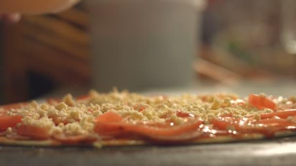 Vaření pizzy. 3 výstřely. Pomalu motion.1. Ženské ruce posypeme sýr pizza. Úzká-up.2. ženské ruce šíří sýra na pizzu. Horní view.3. Pánev s pizzou se umístí do sušárny