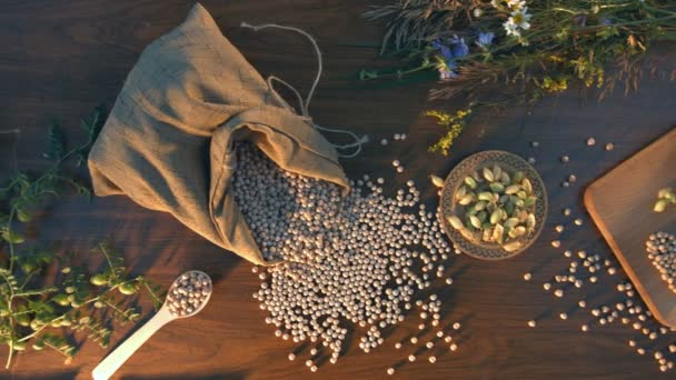 Still life with chickpeas on the table.Top view. The smooth glide of the camera over the table on which is a bag with chickpeas, a saucer and jar with chickpeas and green branch.On the table is a bouquet of wildflowers.