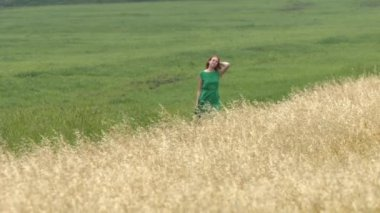 A walk between two fields. Slow motion. A beautiful red-haired girl in a green dress is walking between the yellow and green fields. She smiles.