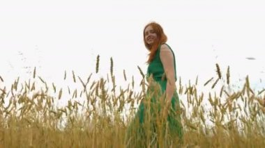 Walk in the mature field.Slow motion. A beautiful red-haired girl in a green dress is walking along the yellow field (oats and wheat).She smiles. The camera moves next to her. Bottom view.