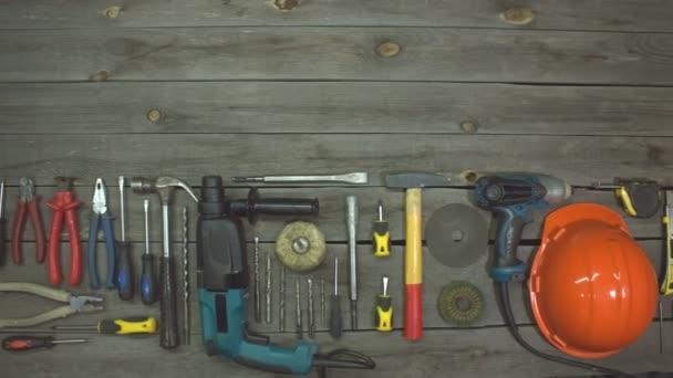 Různé elektro a ruční nářadí. Horní pohled. Na stole jsou nástroje pro různé typy stavebních a opravárenských prací na dřevě, kovu, betonu, plastu a dalších materiálech. Kamera se pohybuje zprava doleva.