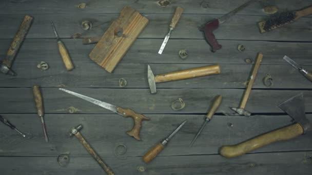 Různé elektro a ruční nářadí a speciální oblečení. Na stole jsou nástroje pro různé typy stavebních a opravárenských prací na dřevě, kovu, betonu, plastu a dalších materiálech.
