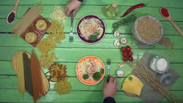 Kóstoló spagetti színes tányérokban az ökoasztalon. Két ember spagettit eszik paradicsomszósszal a vacsoránál. Ízletes hagyományos olasz étel. A közelben olaj, zöldségek, különféle száraz tészták, gombák..