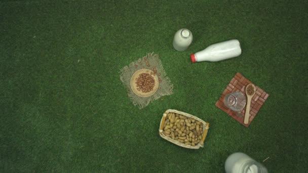 Peanut milk. Top view. Slow motion 2x. Peanut milk and peanuts on the lawn. A male hand puts a jug of milk on the grass.