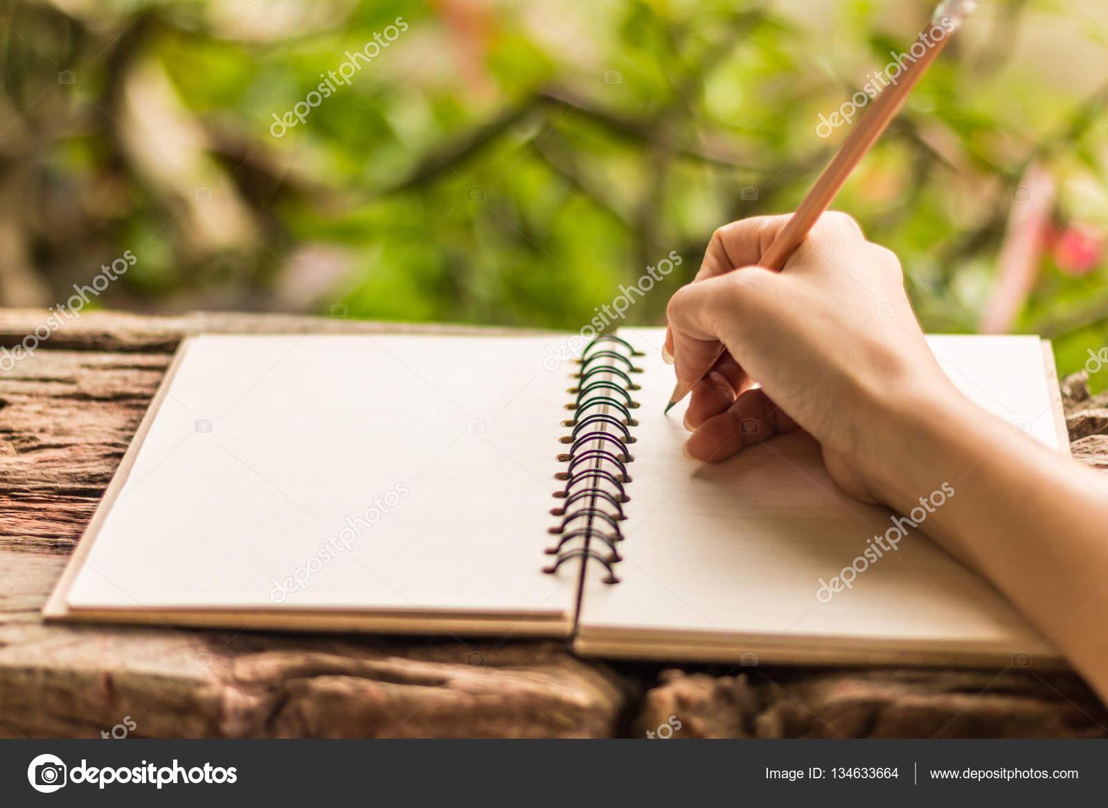 hands of girl writing - hands of girl writing with a pencil in