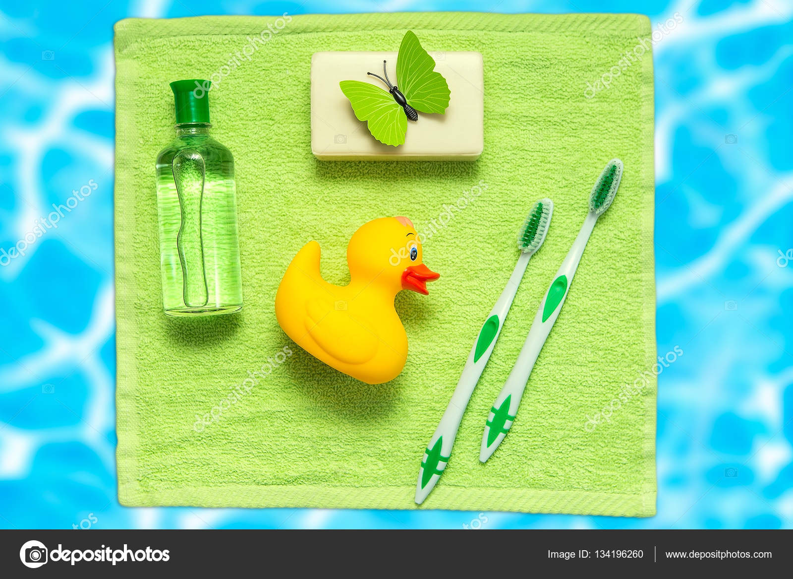 Bathroom Accessories On A Green Towel Rubber Ducky Toothbrushes