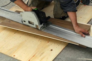 Worker measures and saws off fragments of steps for stairs