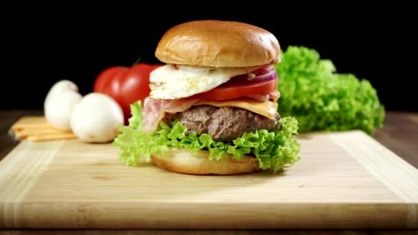 Uvařený velký burger s masovou kotletou a zeleninou.