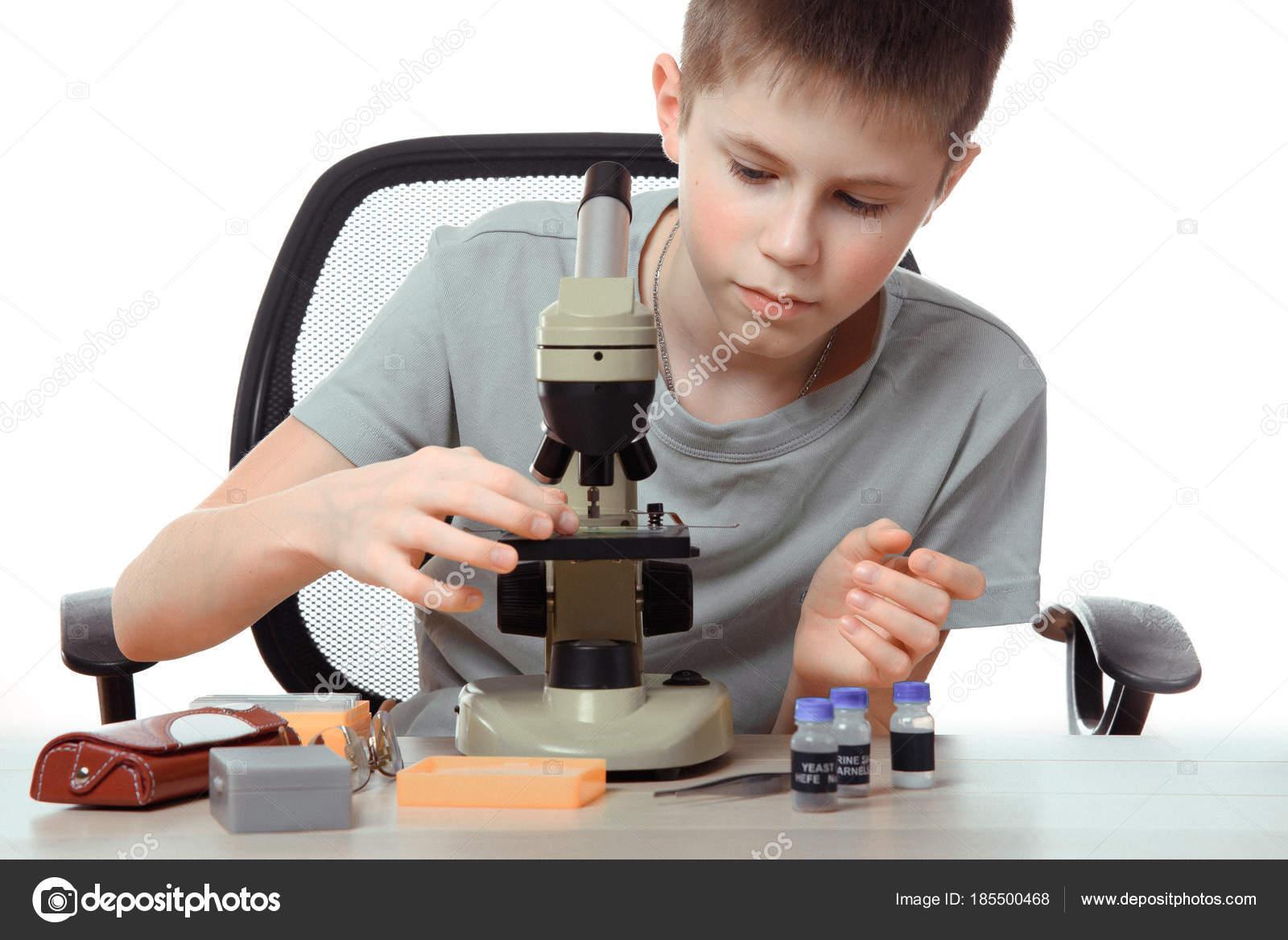 Teen junge im schullabor. forscher arbeiten mit mikroskop