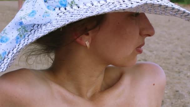 Fiatal nő, a strandon napozással kalap