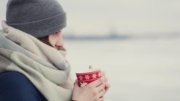 Mladá žena se těší její ranní kávu nebo čaj na pozadí zasněžený horizont při chůzi