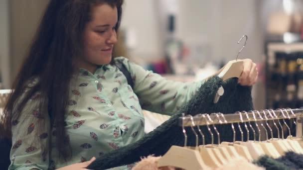 mladá žena v obchodě vybrat teplé zimní oblečení