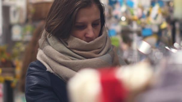 eine junge Frau im Laden wählt warme Winterkleidung