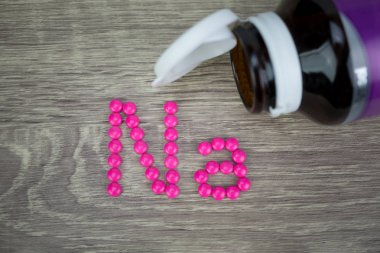 Pink pills forming shape to Na alphabet on wood background