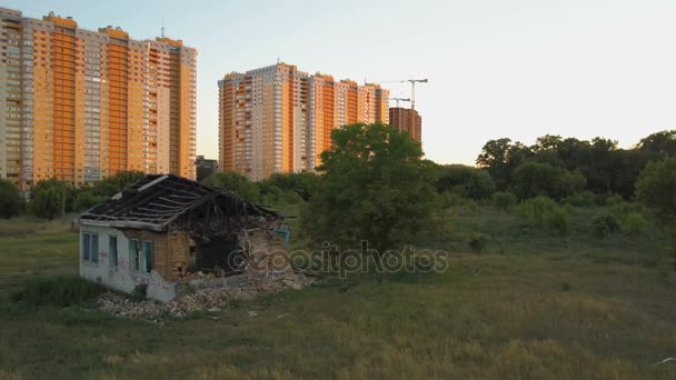 A lonely old ruined house stands near with new multi-story apartment buildings. Aerial view