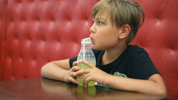 A boy drinks lemonade in a cafe on a red couch