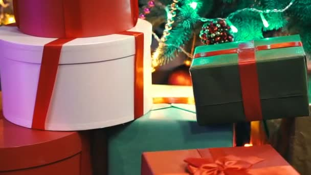 Multicolored boxes with gifts lie under the Christmas tree. Christmas gifts in festive packaging. Close-up