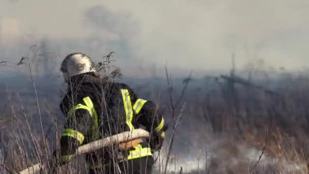 Hasič hasí lesní požár poblíž města. Mezi keři a stromy hořela tráva kouřem. Znečištění ovzduší a ekologie. Požáry způsobené suchem a změnou klimatu. Žhářství. Hasiči