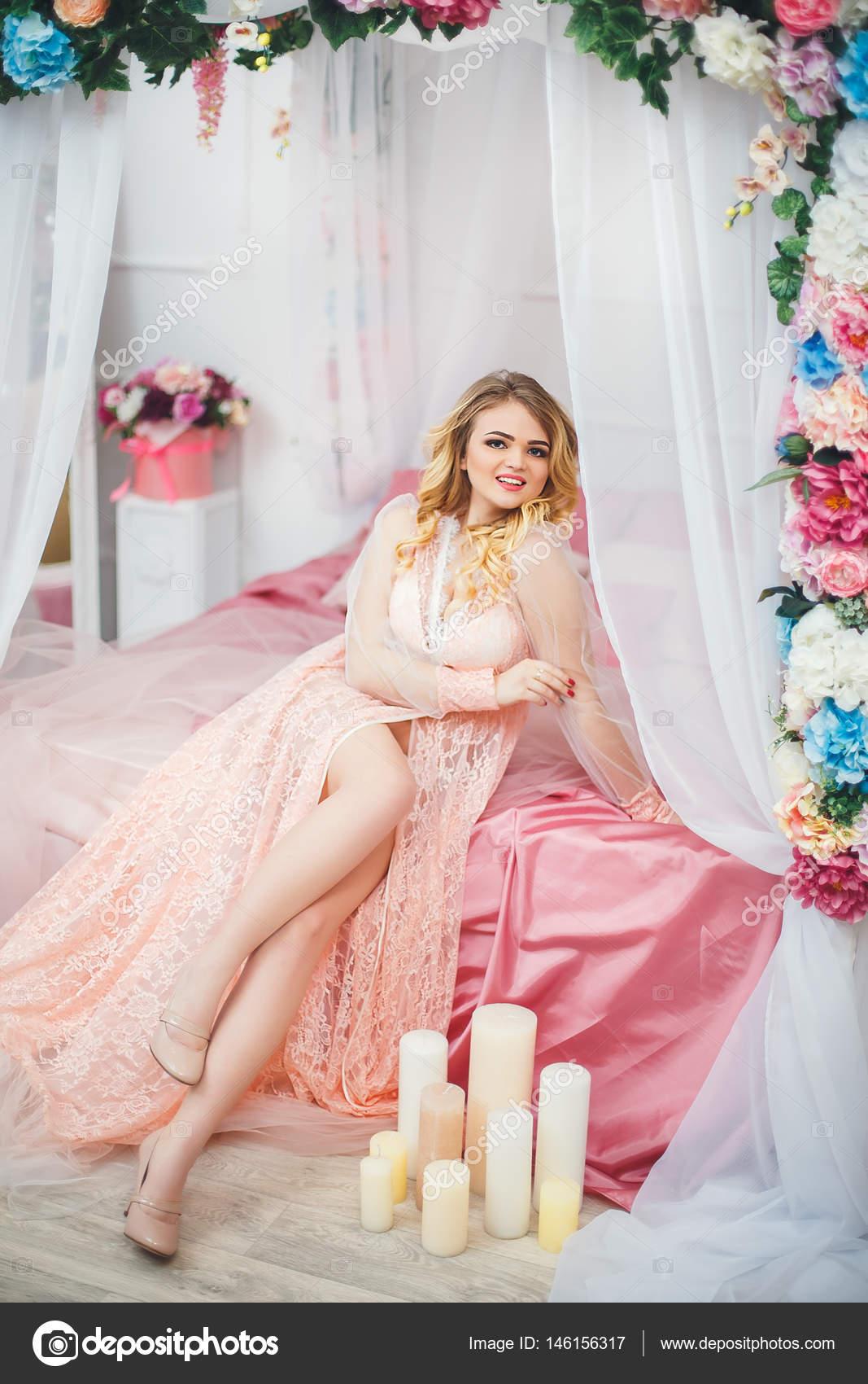 Joven bonita a mujer en bata romántico en cama decorada con flores ...