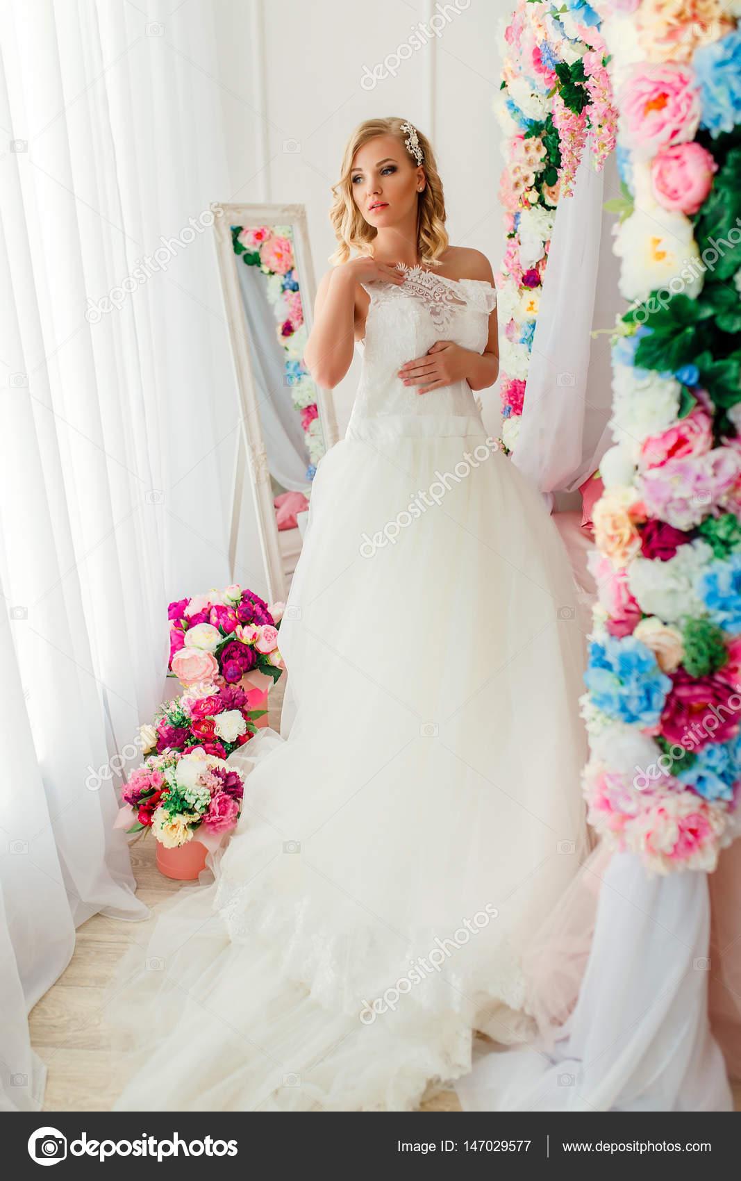 Junge Frau trägt Hochzeitskleid posiert in Zimmer mit Blumen ...