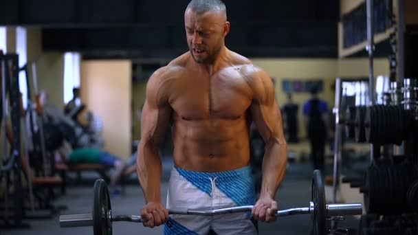muskulöser Bodybuilder, der im Fitnessstudio Übungen auf dem Bizeps mit großer Hantel macht