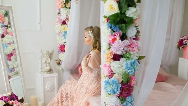 Young blonde pretty woman in romantic negligee sitting on bed decorated with flowers and looking at herself in the mirror.