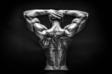 Back view of tattoed bodybuilder with outstretched arms