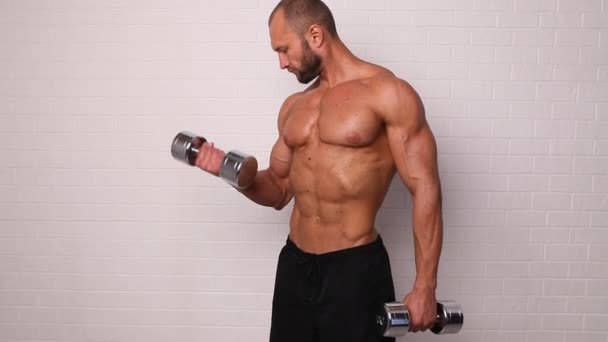 Strong topless man doing exercise with dumbbells