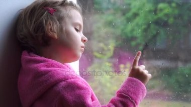 Close up of a Little cute girl in pink bathrobe stares sadly out of a window. Sitting on the window sill.