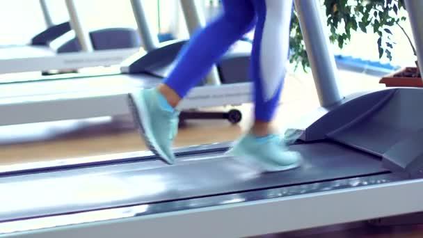 junge Fitness-Frau macht Cardio-Übungen im Fitnessstudio, die auf einem Laufband läuft.