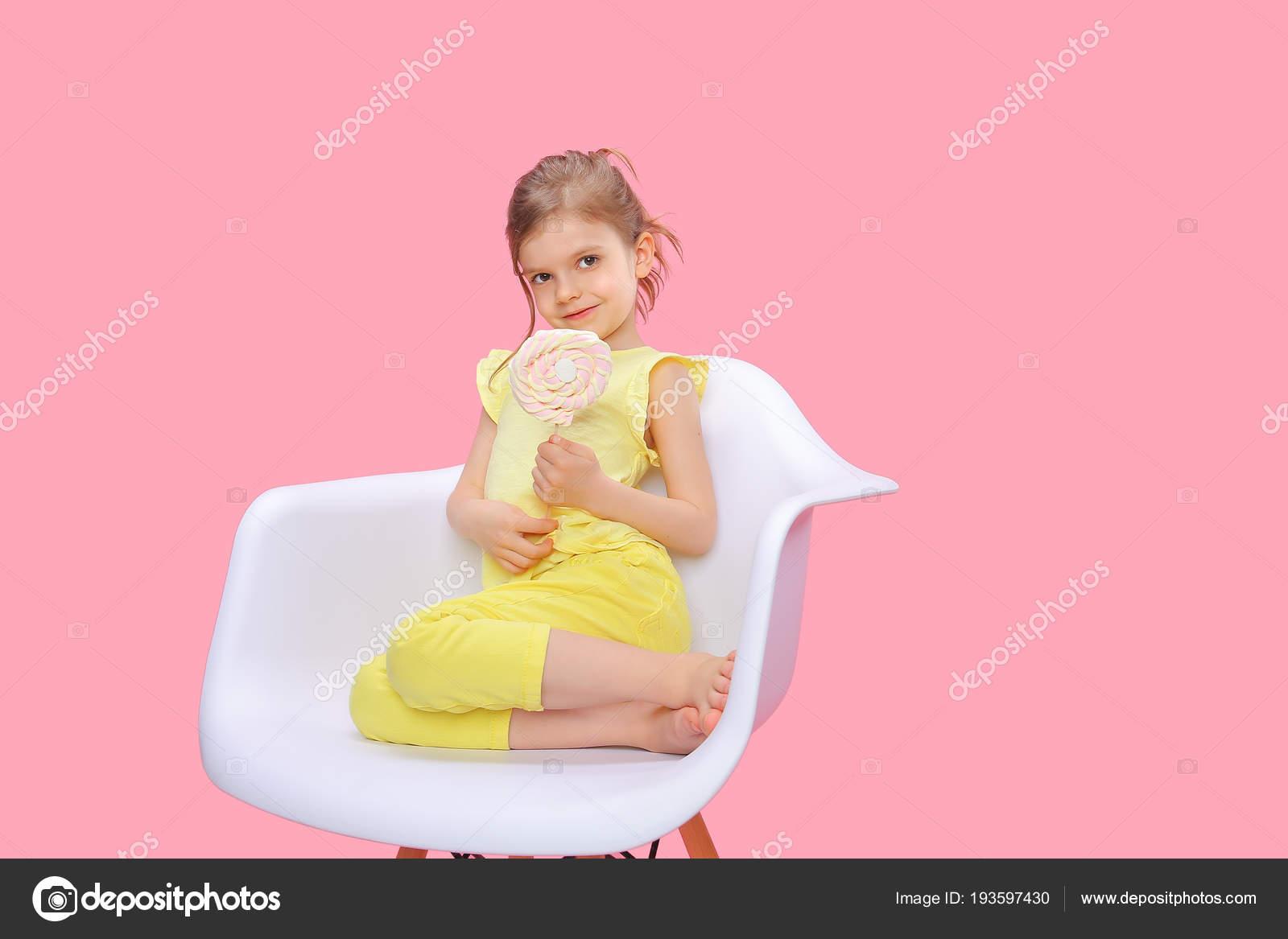 Content Mädchen Mit Süßigkeiten Im Stuhl Stockfoto Zamuruev