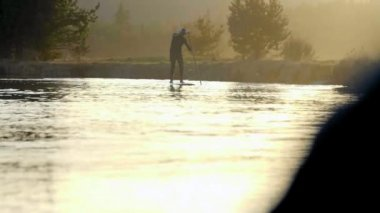 Man in wetsuit paddleboarding