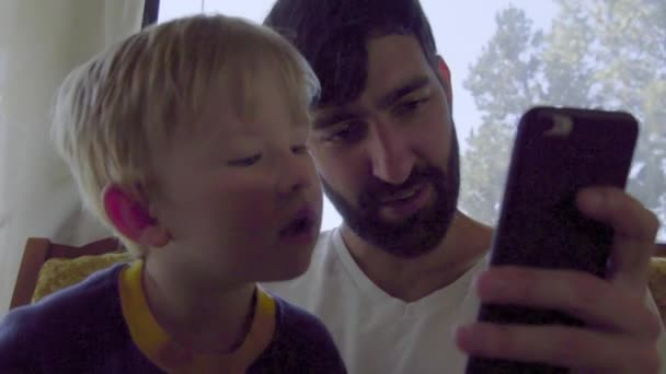 2236cd439785 Chłopczyk ma bliżej przyjrzeć się telefon komórkowy gry– filmik stockowy