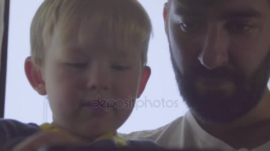 Boy and father using cell phone