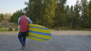 Bearded man walks with paddleboard