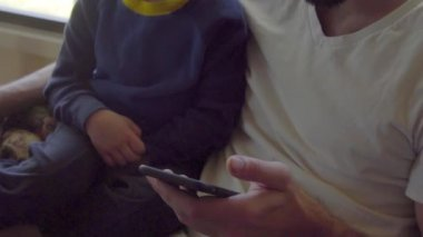 Son and father using smartphone