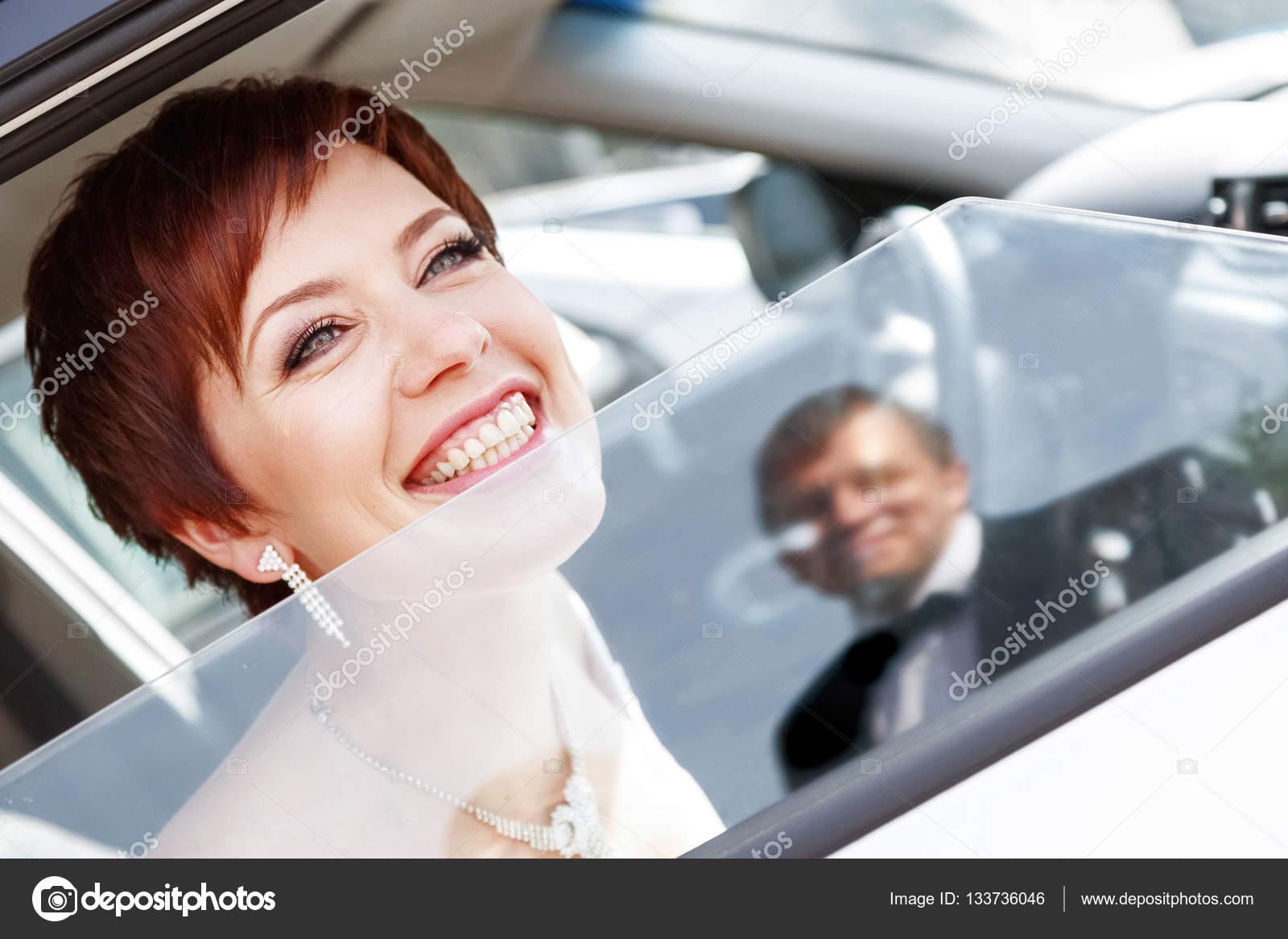 bröllop 35 år Rödhåriga rolig brud i bil leende brudgummen. Kvinna 35 år  bröllop 35 år