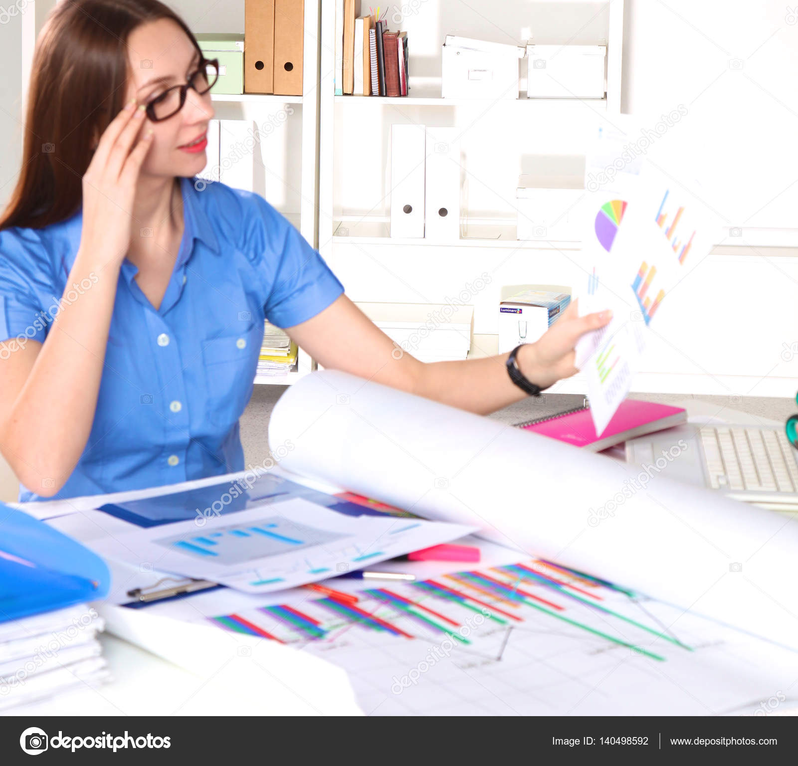 Young graphic designer working on laptop using tablet at home ...