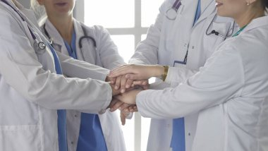 Team of medical workers holding hands together indoors, above view. Unity concept