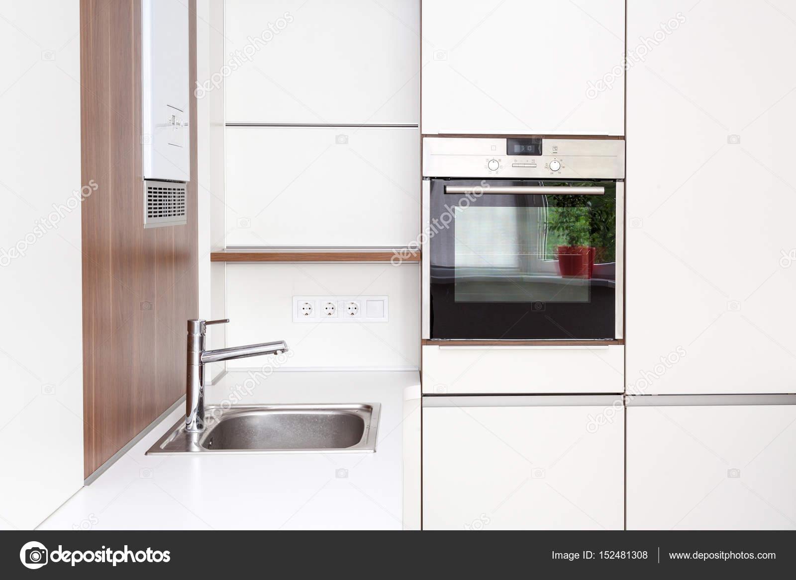 Nieuwe moderne witte keuken met ingebouwde oven en chroom water