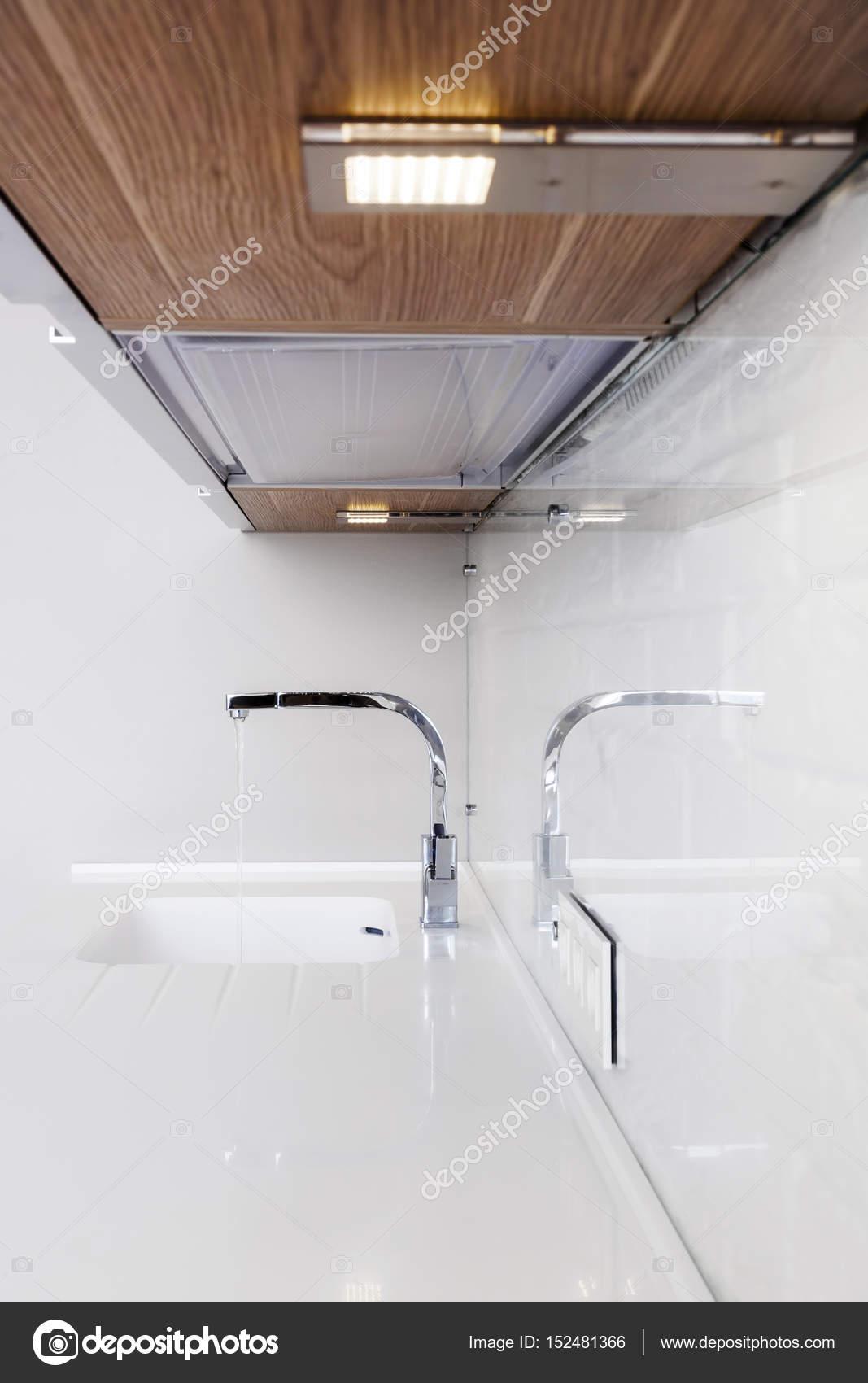 Detail of a rectangular designer kitchen sink with chrome water tap ...