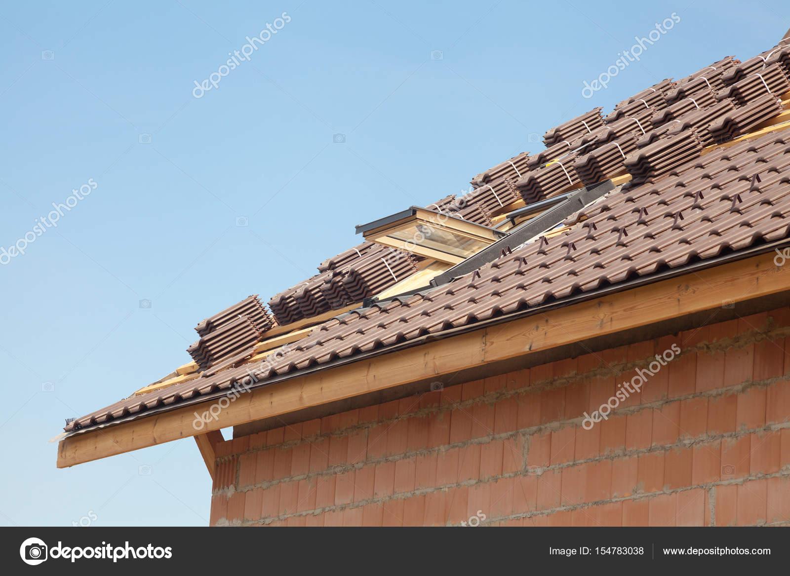 Nouveau toit avec lucarne ouverte, des tuiles rouges naturels contre ...