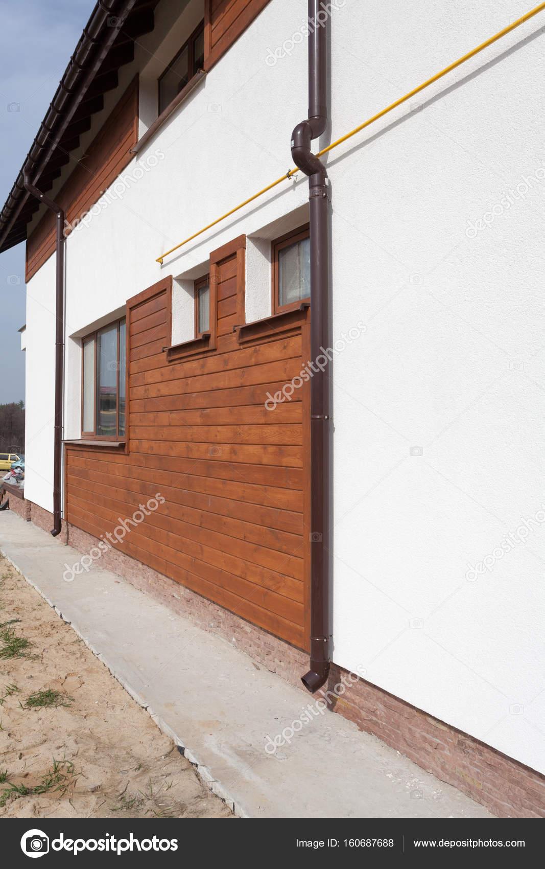 neue braun kupfer dachrinne im haus mit weißen wand und holzbohlen
