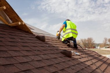 Construction worker putting the asphalt roofing (shingles) with nail gun on a large commercial apartment building development.