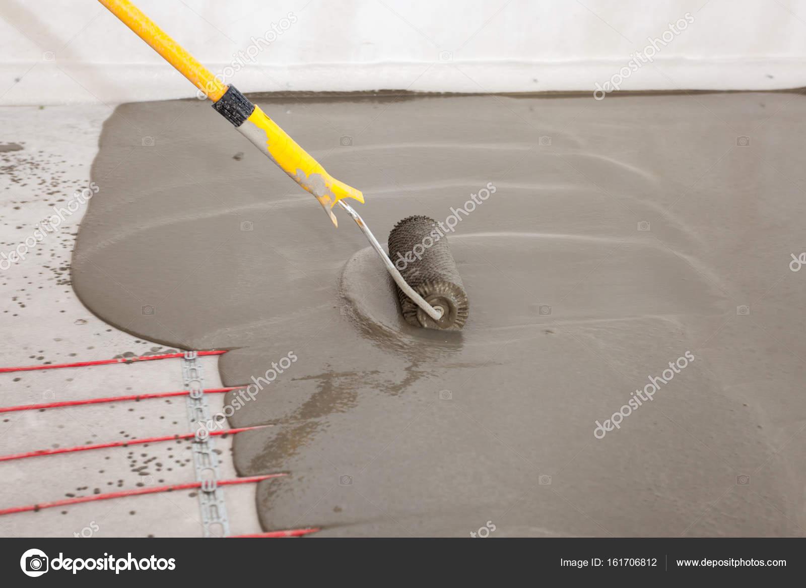 Elektrische Fußbodenheizung System Installation Im Neuen Haus. Arbeiter  Ausrichten Zement Mit Walze U2014 Foto Von Brizmaker