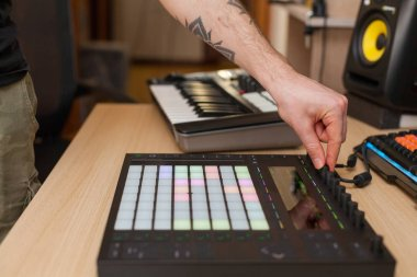 Producer makes a music on professional production controller with push button pads