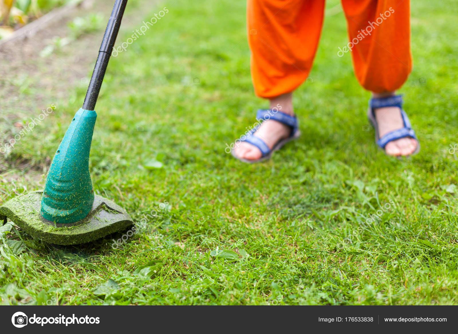 c92011000 Benzin gyep trimmer mows lédús zöld fű a pázsiton, egy napsütéses nyári  napon. Közeli kép: szelektív fókusz a kép. Kerti berendezések.