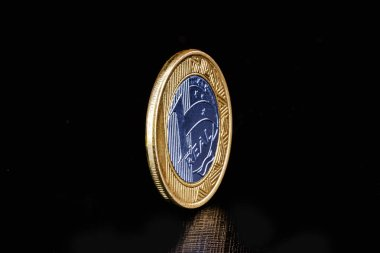 Brazilian real coins, with golden tone. Banking savings or investment concept. Coins a real selective focus.